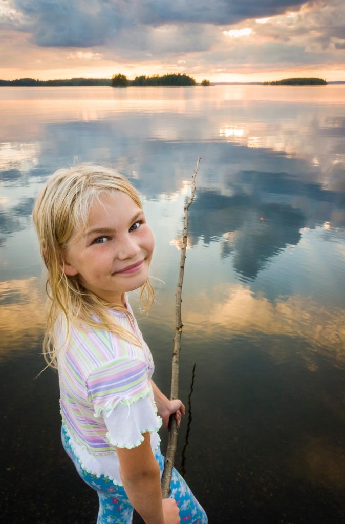 En flicka som fiskar vid en sjö.