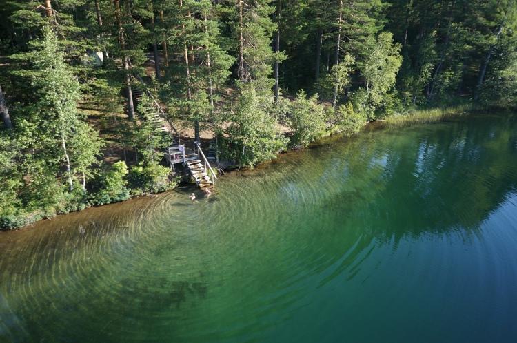 En trappa i trä som leder från skogen till vattnet vid en sjö.